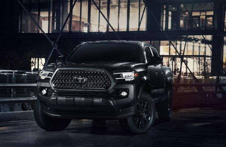 Black 2021 Toyota Tacoma Nightshade Edition on a City Street at Night