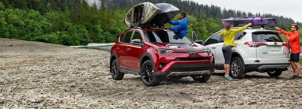 Red and White 2018 Toyota RAV4 Models By a Lake
