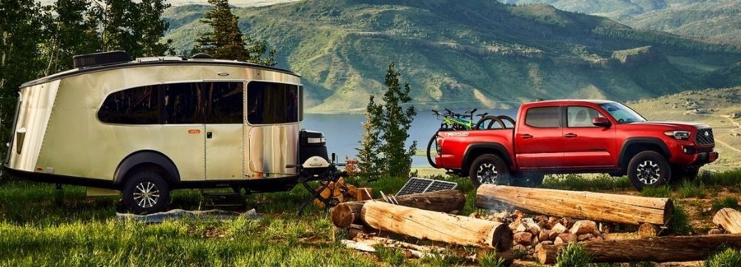 Red 2021 Toyota Tacoma and Trailer by a Mountain Lake