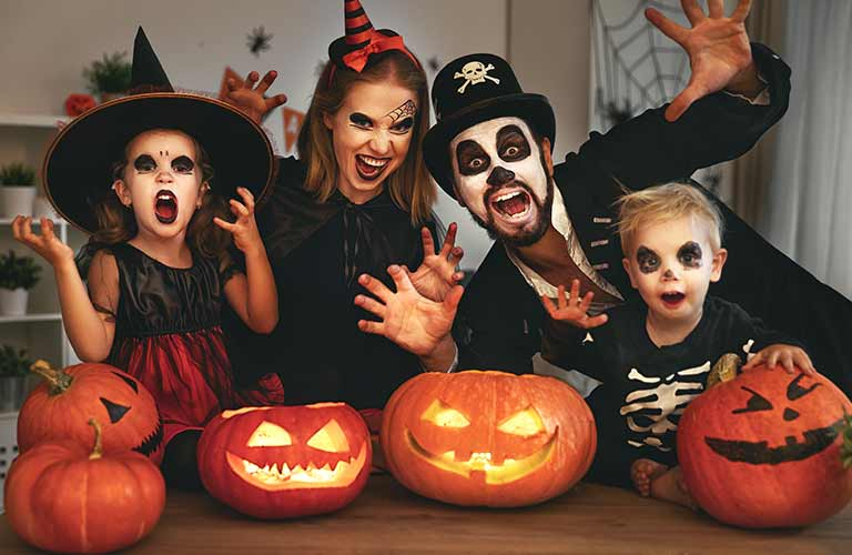 Family in Halloween Costumes with Jack-o-Lanterns