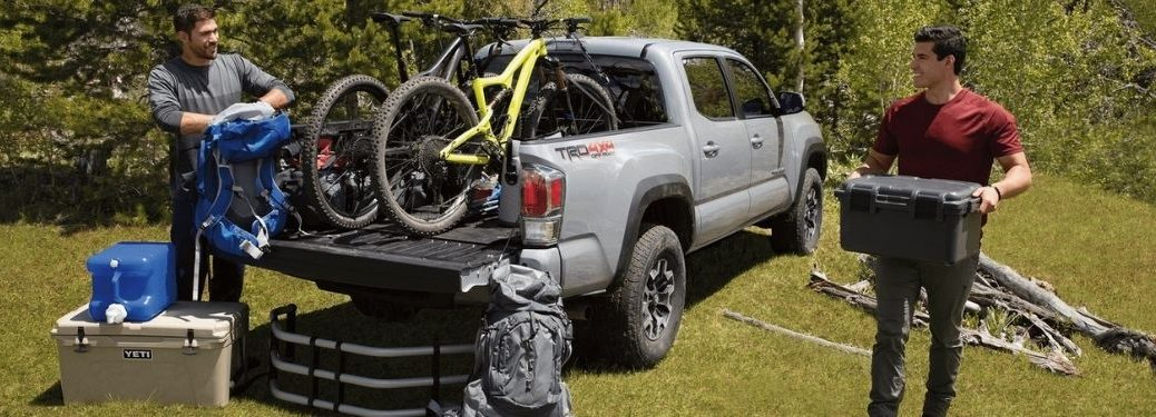 Two Men Unloading Cargo From the Bed of a 2021 Toyota Tacoma