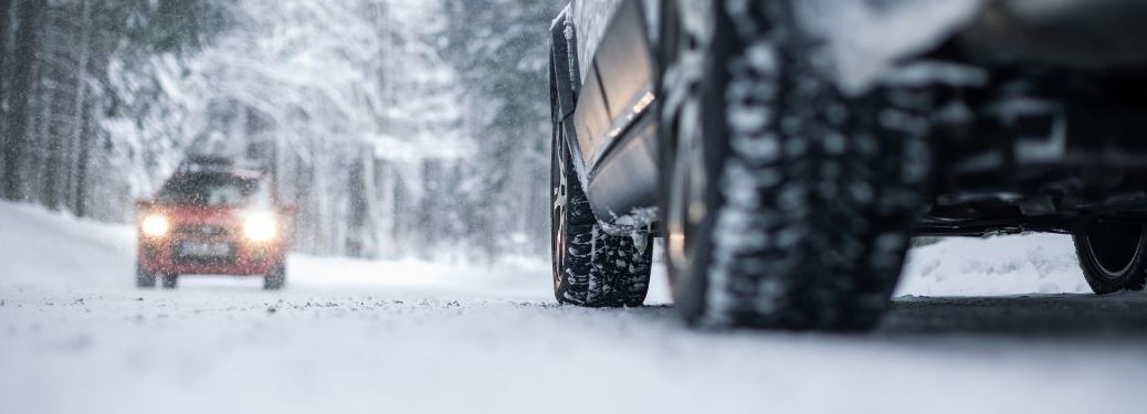 Close Up of Tires in Snow and Another Car on a Snowy Road