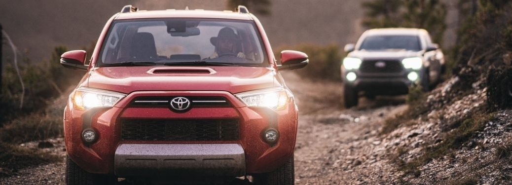 Red 2021 Toyota 4Runner and Silver 2021 Toyota Tacoma on a Trail