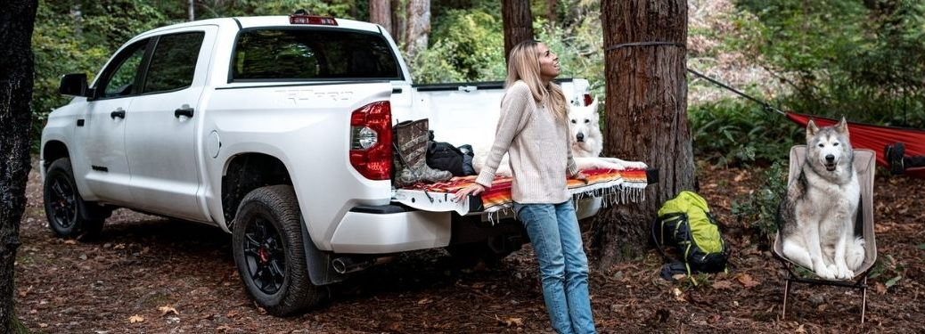 Woman Sitting on the Tailgate of a White 2021 Toyota Tundra at a Camp Site