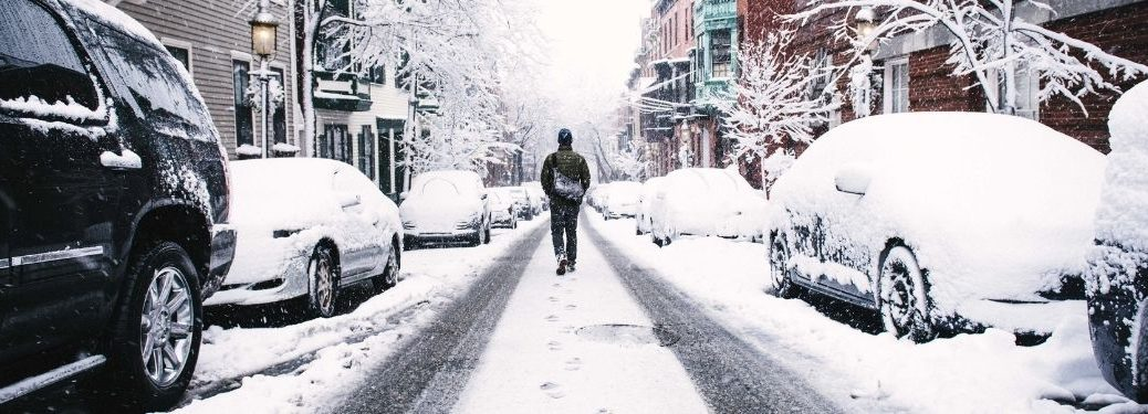 Man Walking Down the Middle of a Snowy Street