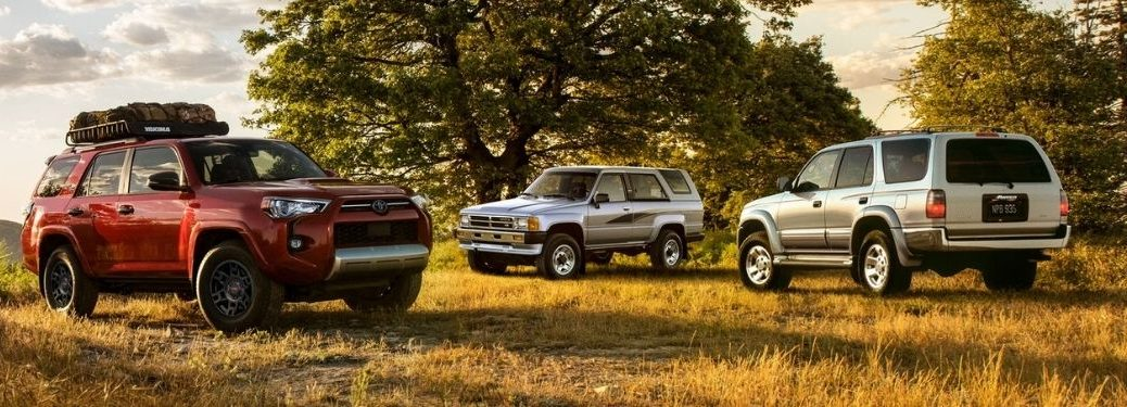 Red 2021 Toyota 4Runner and Older Silver Toyota 4Runner Models in a Field