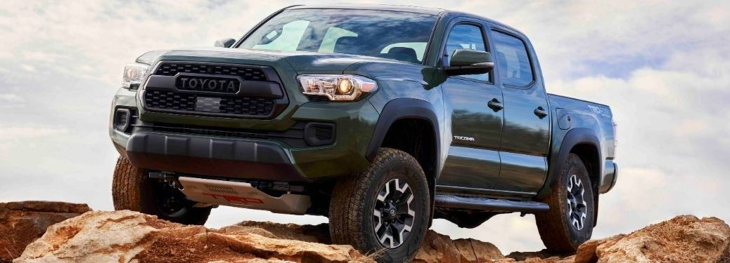 Green 2021 Toyota Tacoma with a Lift Kit on a Rocky Trail
