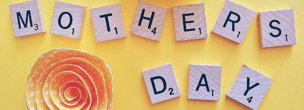 Scrabble Tiles Spell Mother's Day on Yellow Background