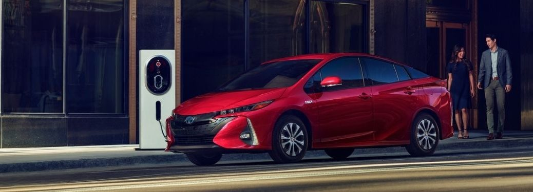 Red 2021 Toyota Prius Prime Charging on a City Street