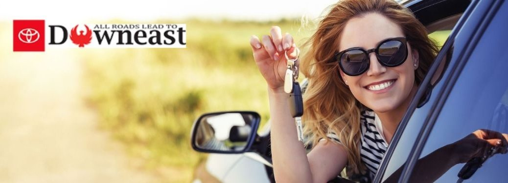 Young Woman in New Car with Keys by Downeast Toyota Logo