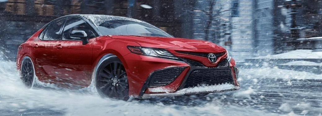 Red 2022 Toyota Camry with AWD Driving in Snow