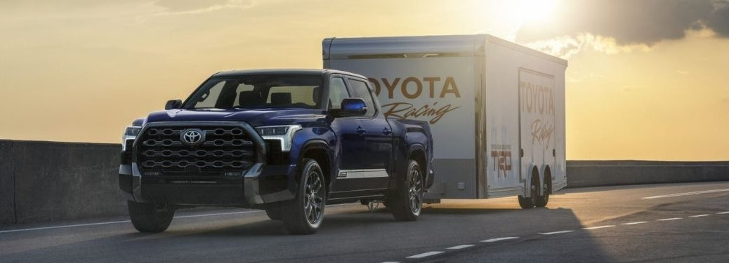 Blue 2022 Toyota Tundra Towing a Trailer at Sunset