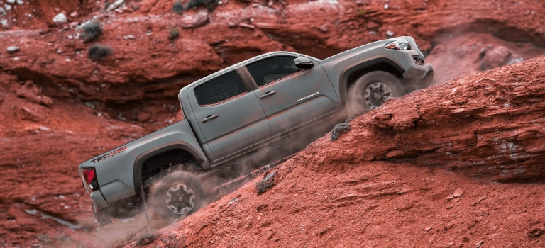 2019 Toyota Tacoma gray side view going up a hill in the desert