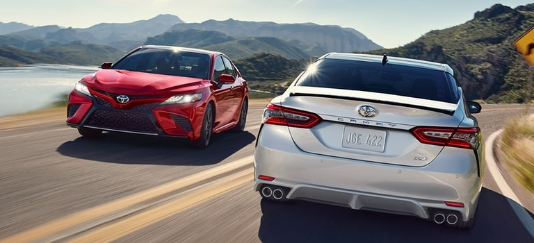 2019 Toyota Camry models red and silver passing eachother on the road