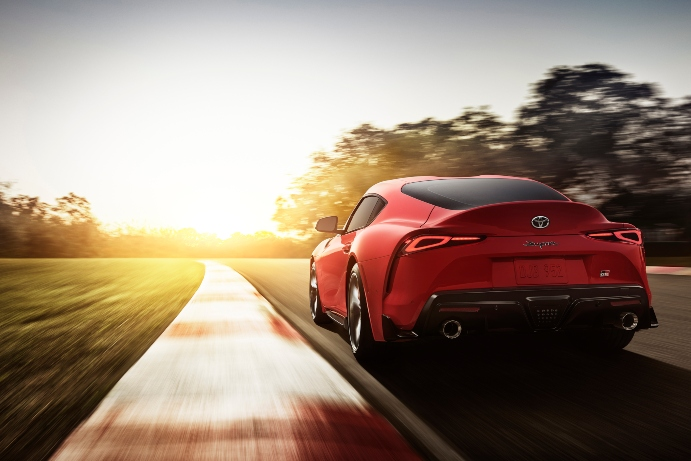 2020 red toyota supra driving into sunset