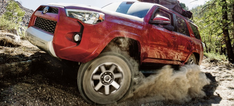 2019 Toyota 4Runner red side view tire spinning in dirt
