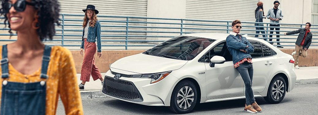 2020 Toyota Corolla white side view being guarded by hipsters