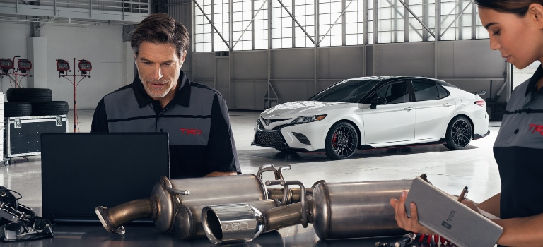 2020 Toyota Camry TRD exhaust system with techs looking on