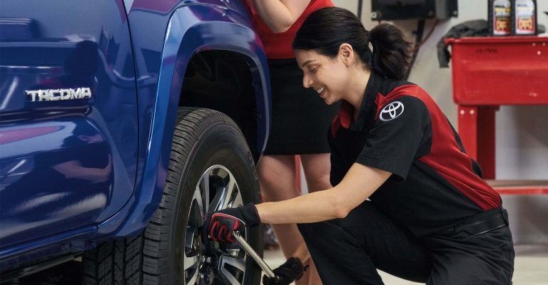 Woman working on the tire of a Tacoma