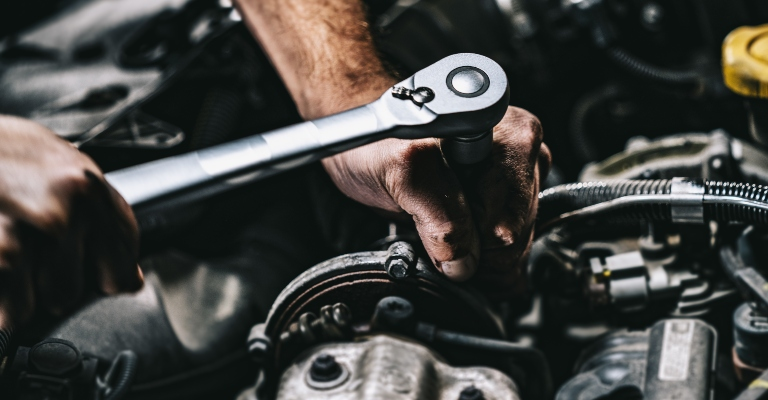 mechanic using a wrench on an engine