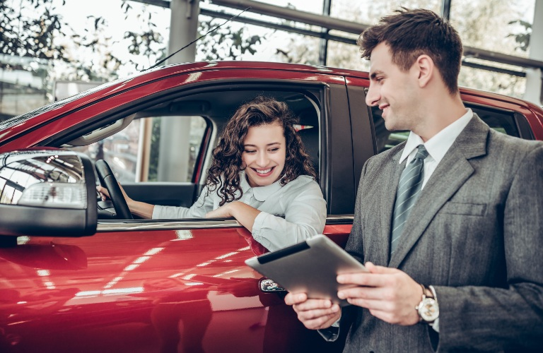Man showing woman car info on a tablet