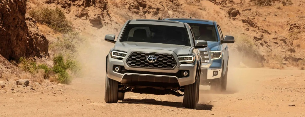 2020 Toyota Tacoma followed by a Tundra in the desert