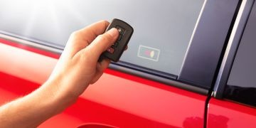 Image of a person holding remote starter near the window of a vehicle