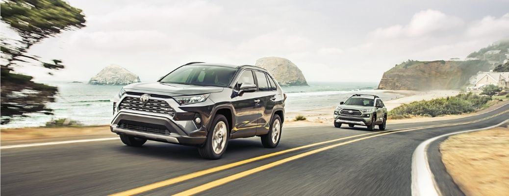 Exterior view of two 2021 Toyota RAV4 models driving down the road