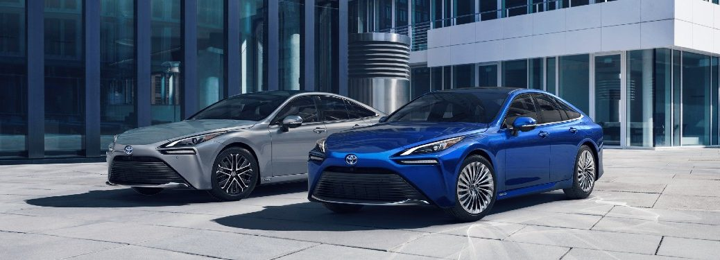 one blue and one silver 2021 Toyota Mirai model parked outside of building