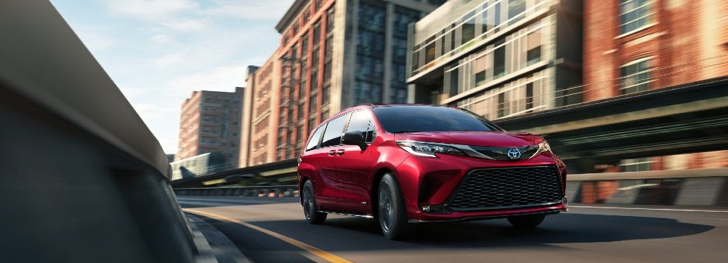 2021 Toyota Sienna red exterior front fascia driving on city bridge