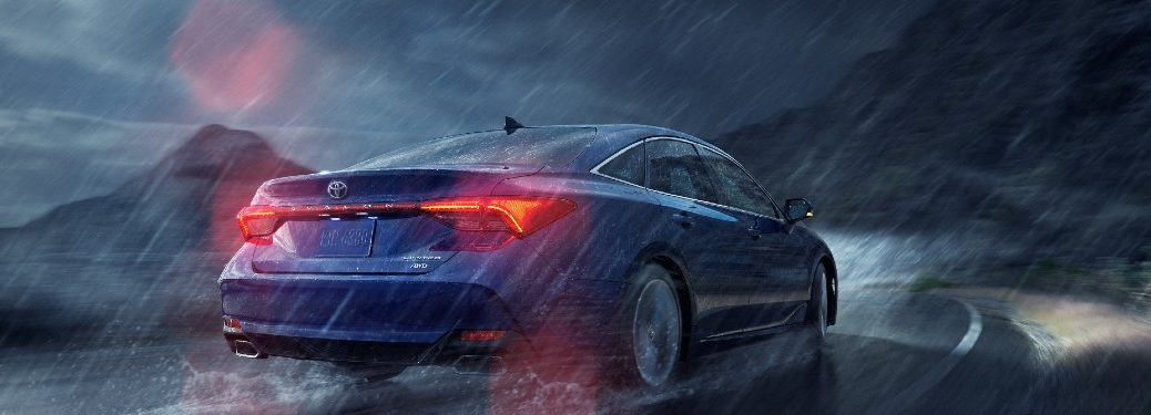 2021 Toyota Avalon blue exterior rear fascia driving on curvy highway during thunderstorm