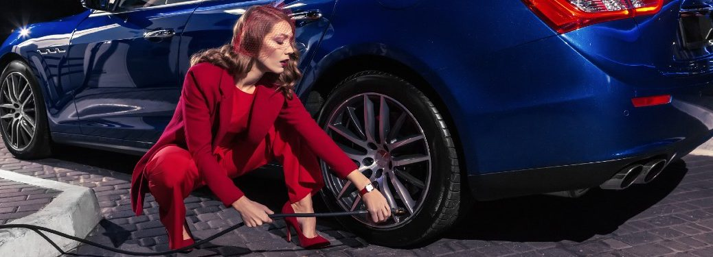 woman in red stylish red pantsuit and heals filling up tires of blue sports car
