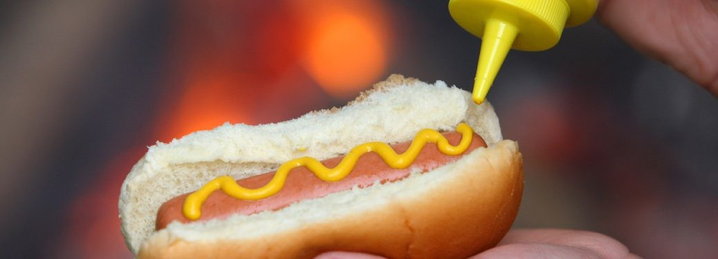 person putting yellow mustard on to a hot dog