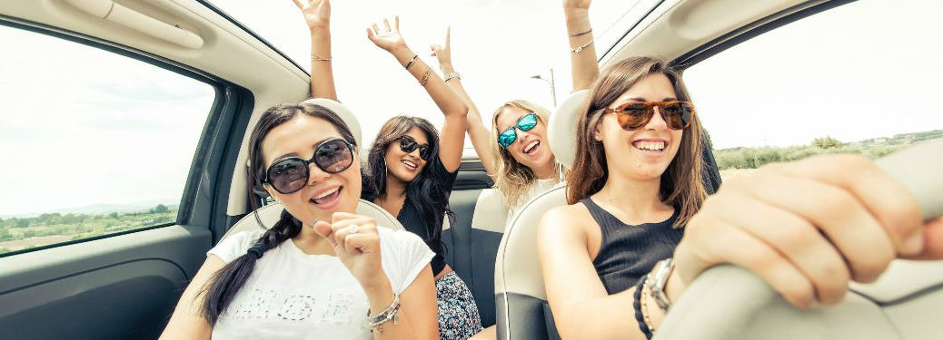 women packed into a car celebrating a road trip