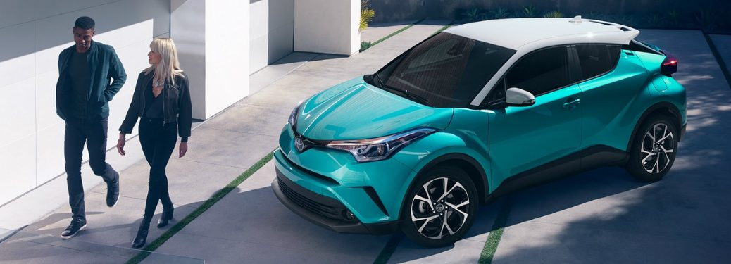 couple walking away from 2018 Toyota C-HR parked in driveway