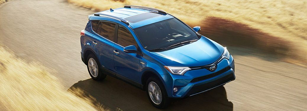 blue 2017 Toyota RAV4 driving on desert road exterior front top view