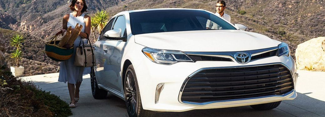 man and woman approaching white 2018 Toyota Avalon Hybrid