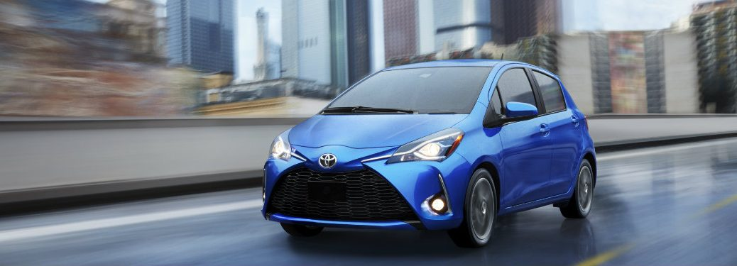 Blue 2018 Toyota Yaris driving on highway in front of skyscrapers