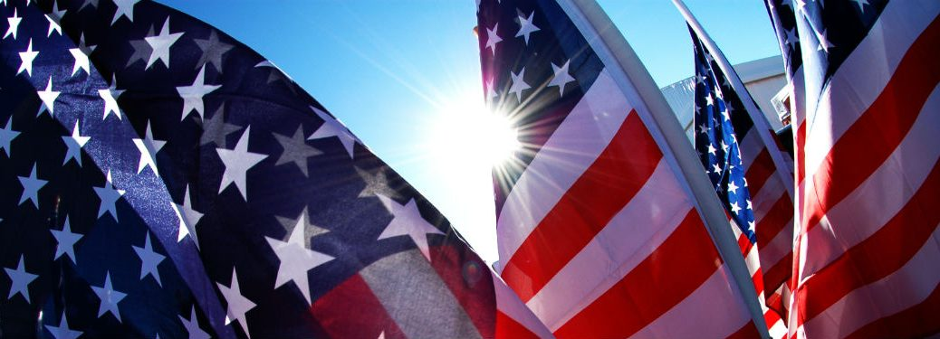 4 American flags close up with sun shining behind them