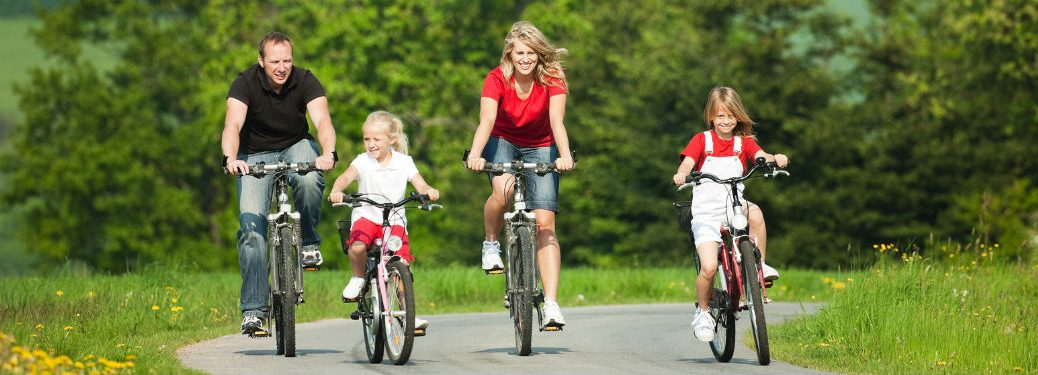 family of 4 riding bikes on back road