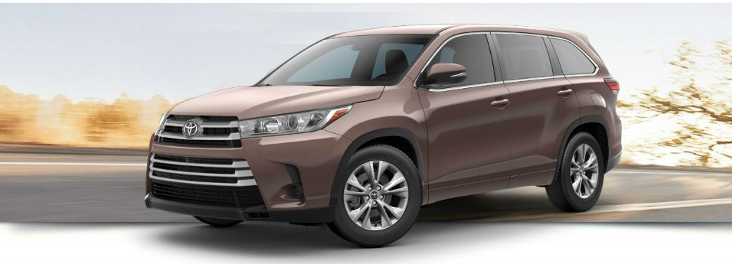 2018 Toyota Highlander LE exterior front fascia and drivers side with blurred road and tree