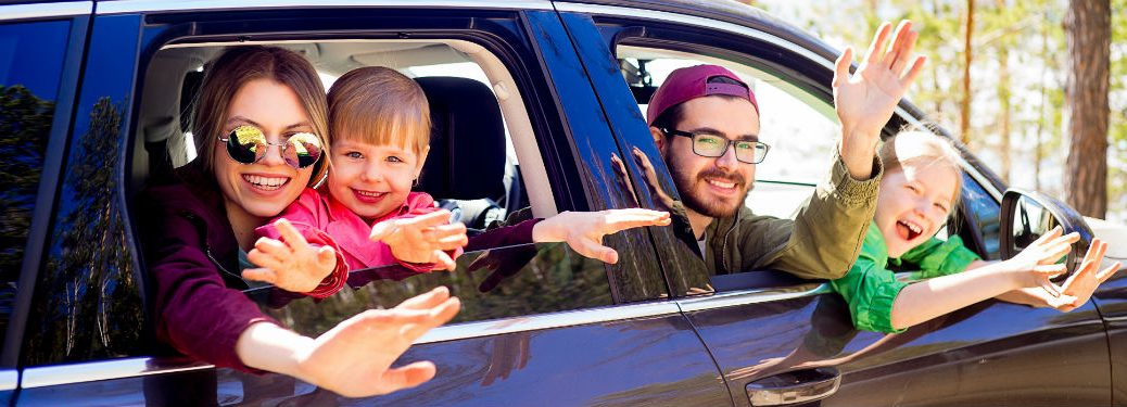 family of four leaning out of car windows