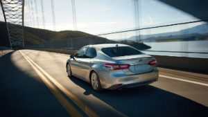 2019 Toyota Camry exterior back fascia and drivers side going fast on blurred bridge