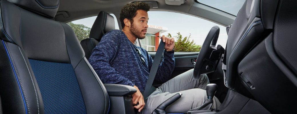 2019 Toyota Corolla interior shot of a man strapping in his seat belt in the driver's seat