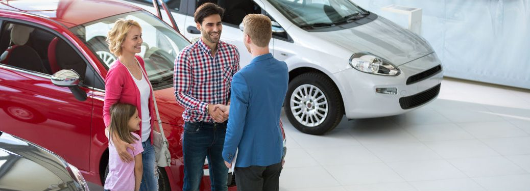 family shaking hands with dealership