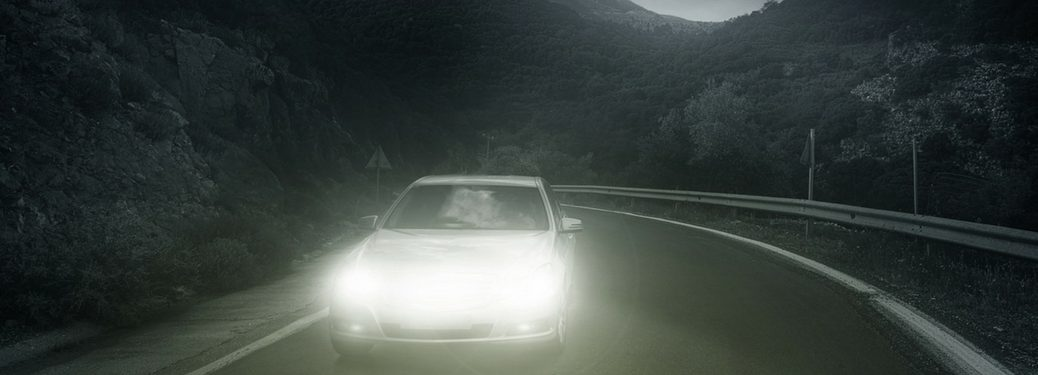 car driving with headlights on at night