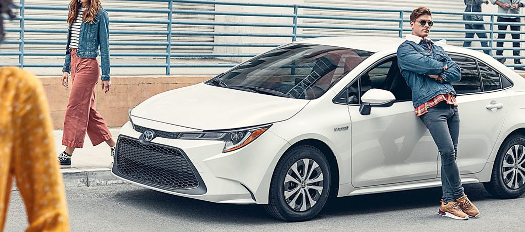 person leaning on parked 2020 Toyota Corolla