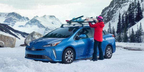 Woman Putting a Snowboard On Top of a Blue 2020 Toyota Prius in the Snow