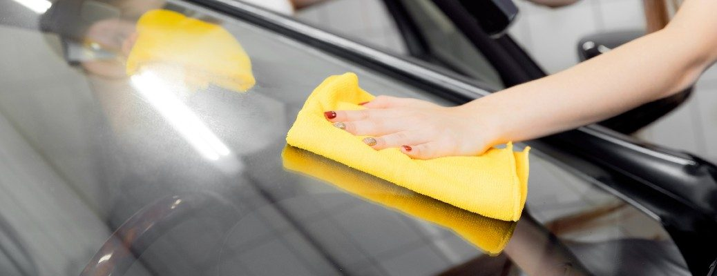 hand cleaning a car window