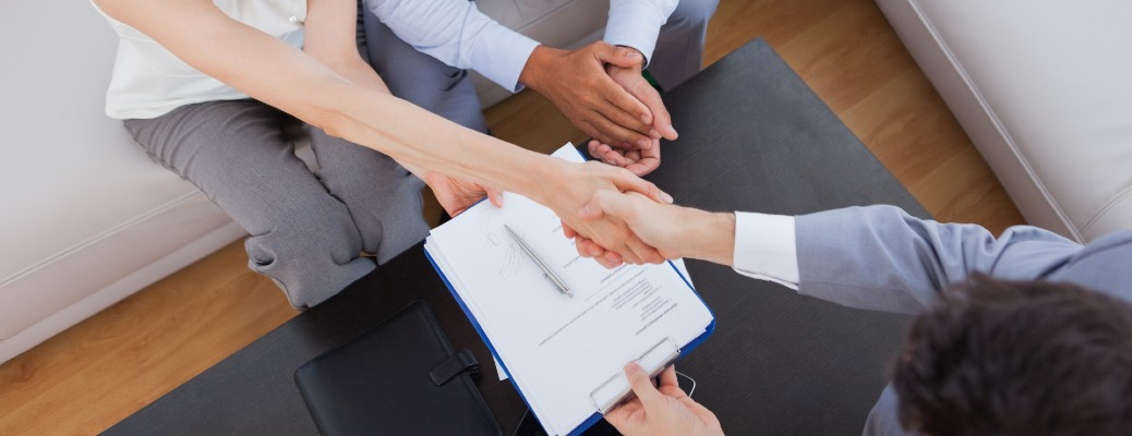 A top view of a woman and salesperson shaking hands after a deal.